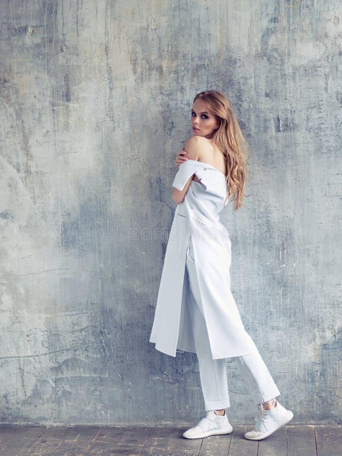 Полный портрет пальто, брюк и тапок дизайна женщины моды нося белых стоковое фото rf
