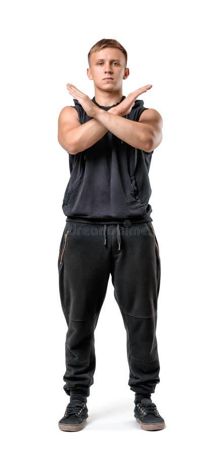 Полный портрет тела красивого muscled молодого человека делая изолированный знак x с его оружиями на белой предпосылке стоковое фото rf