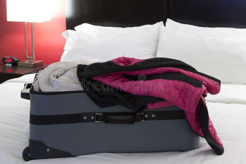 Полный чемодан на кровати стоковые фотографии rf