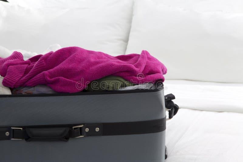 Полный чемодан на кровати стоковое изображение rf