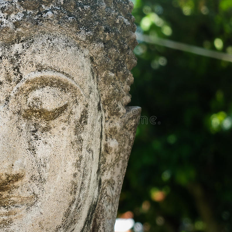 Половина старого каменного Будды смотрит на стоковые изображения