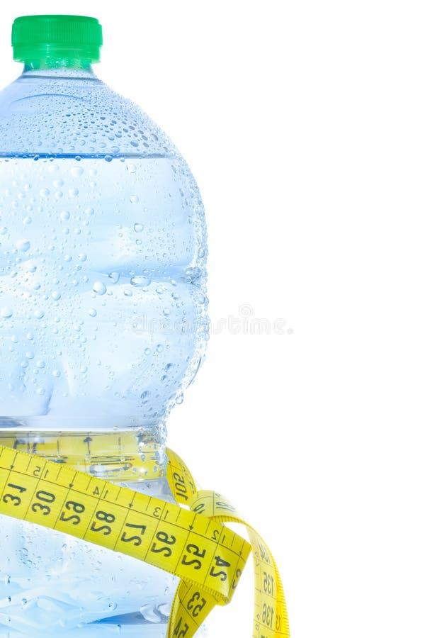 Половинная пластичная бутылка с водой, падениями и измеряя ...