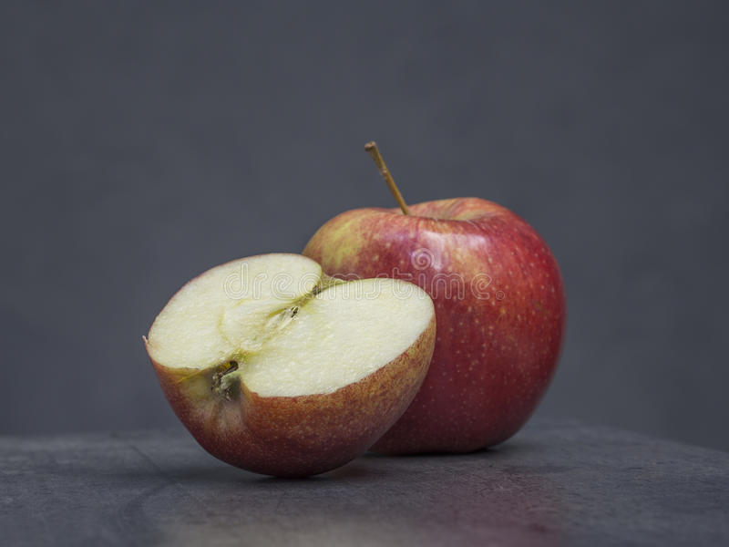 Половинное и одно красное яблоко на серой предпосылке стоковая фотография rf