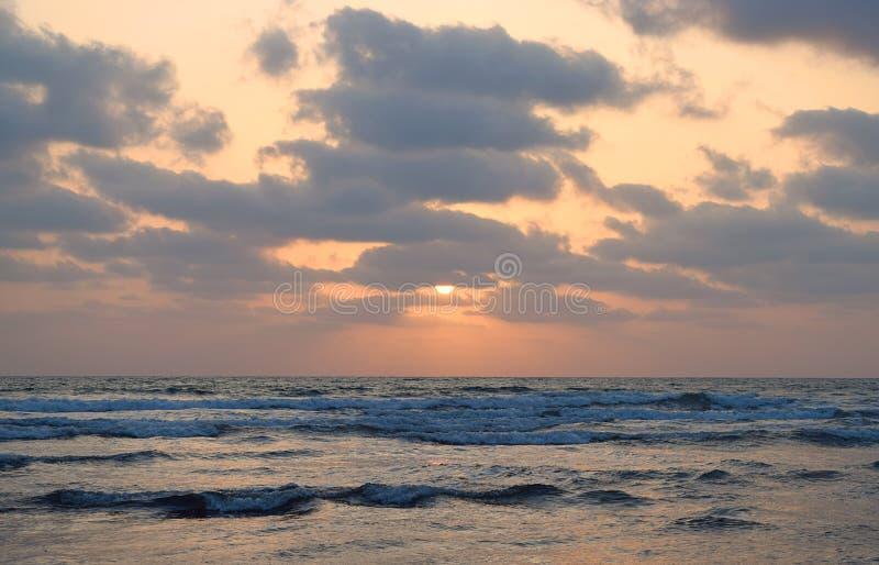 Половинное Солнце под облаками над бесконечным океаном - естественными обоями захода солнца стоковые изображения