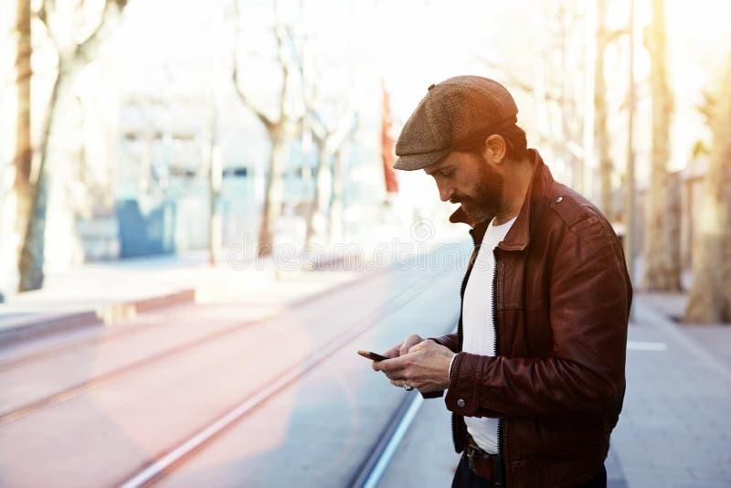 Половинный портрет длины бородатого человека битника одел в стильных одеждах беседуя на телефоне клетки пока стоящ в улице стоковые изображения
