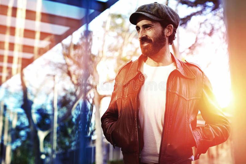 Половинный портрет длины взрослого бородатого человека битника одел в первоклассных стильных одеждах ждать кто-то на улице, стоковая фотография