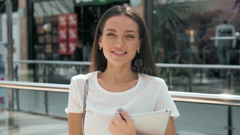 Половинный портрет длины молодой коммерсантки смотря экран сенсорной панели пока стоящ в современном интерьере размеров офиса стоковое изображение rf