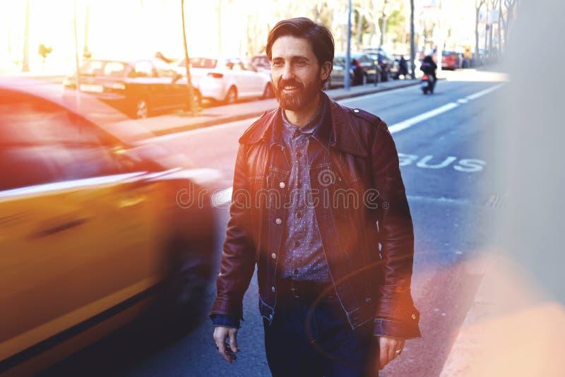 Половинный портрет длины мужчины взрослого усмехаясь красивого одел в первоклассных стильных одеждах идет на дорогу в дне осени, стоковое фото
