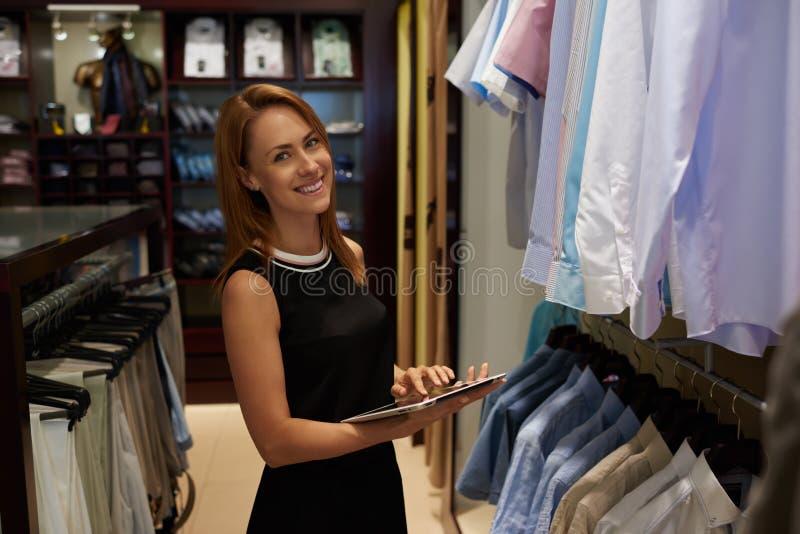 Половинный портрет длины счастливого женского предпринимателя используя цифровую таблетку для работы в ее современном магазине с  стоковое фото