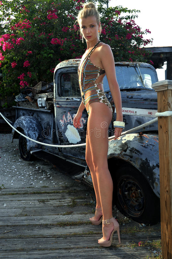 Положение белокурого купальника модельное перед винтажным автомобилем стоковая фотография rf