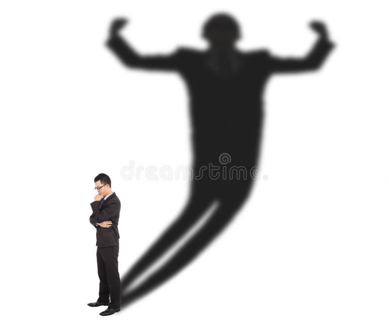 Положение бизнесмена и тень отливки сильного человека стоковые изображения