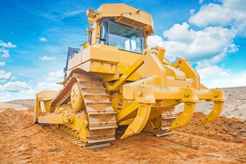 Положение бульдозера покрашенное желтым цветом на заде песка стоковая фотография