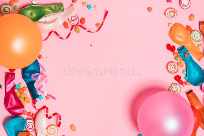 Положение квартиры торжества Конфета с красочными деталями партии на розовом ба стоковые изображения