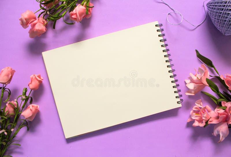 Положение романтичных роз плоское с тетрадью пустой страницы на фиолетовой предпосылке стоковое фото rf