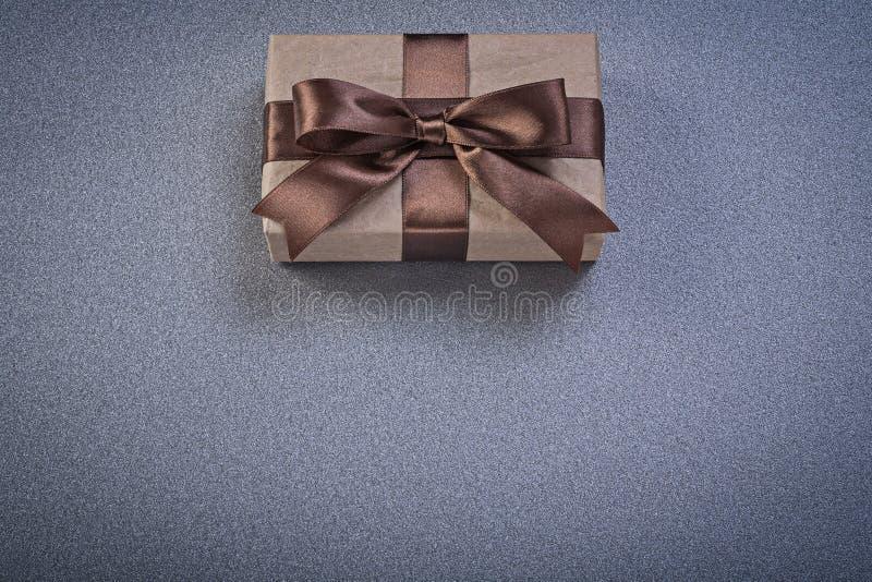Положенное в коробку присутствующее в коричневой упаковочной бумаге на сером directl предпосылки стоковое изображение rf