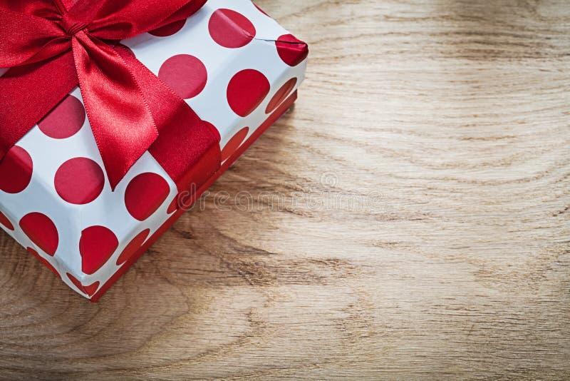Положенное в коробку присутствующее с красной лентой на conce торжеств деревянной доски стоковые изображения rf
