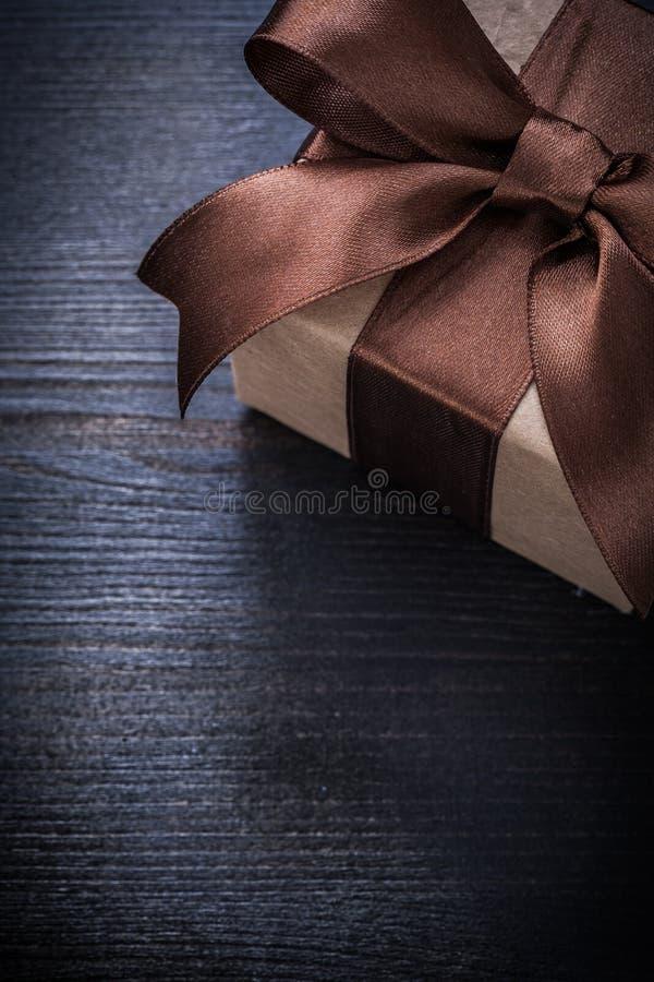 Положенный в коробку настоящий момент в упаковочной бумаге на винтажном деревянном copyspace доски стоковое изображение