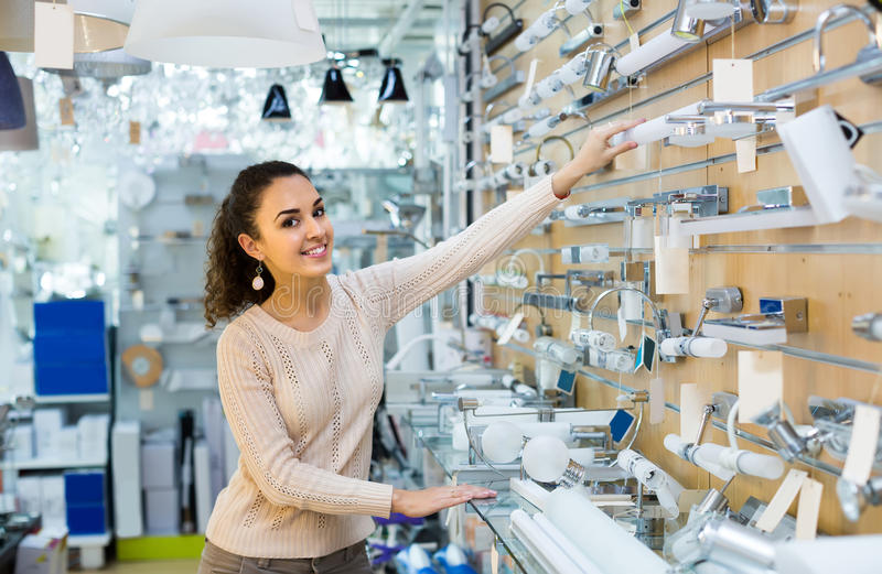 Положительная женщина делая покупки в магазине освещения стоковое фото