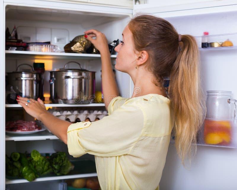 Положительная женщина ища продукты на холодильнике стоковая фотография