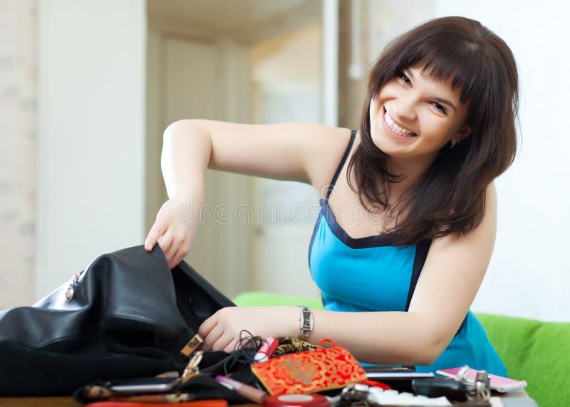 Положительная женщина находя что-нибыдь в портмоне стоковые фотографии rf