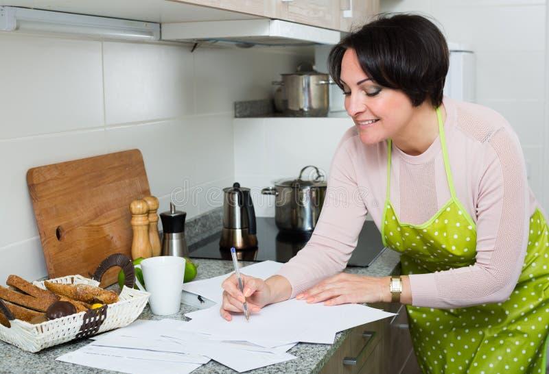 Положительная женщина подписывая финансовые бумаги в кухне стоковое изображение rf