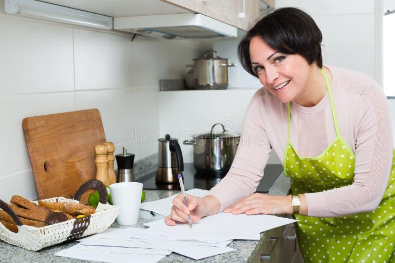 Положительная женщина подписывая финансовые бумаги в кухне стоковое фото rf