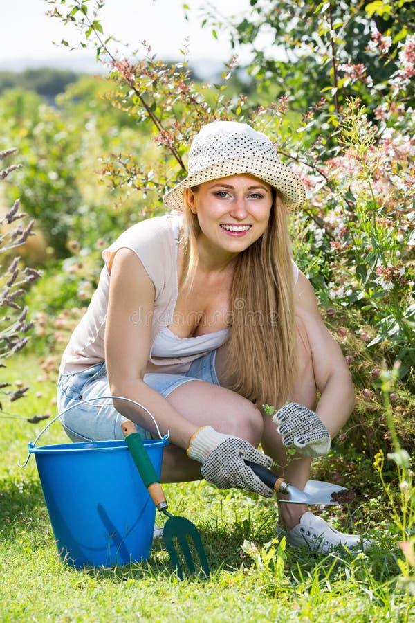 Положительная молодая женщина работая в саде среди зеленых растений и fl стоковые изображения