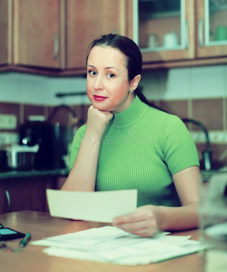 Положительная домохозяйка смотря через счеты стоковые фотографии rf