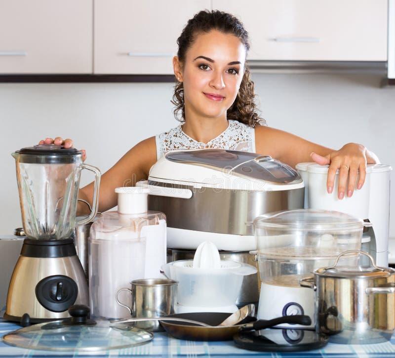 Положительная домохозяйка с кулинарными приборами на кухне стоковое изображение rf