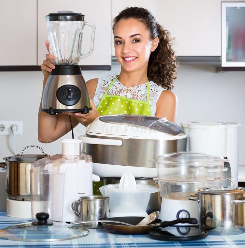 Положительная домохозяйка с blender и kitchenware стоковое фото