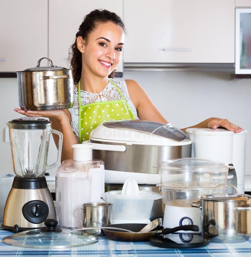 Положительная домохозяйка с kitchenware в кухне стоковое фото