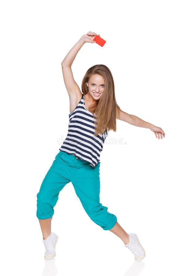 Положительная предназначенная для подростков девушка усмехаясь показывающ кредитную карточку стоковые изображения