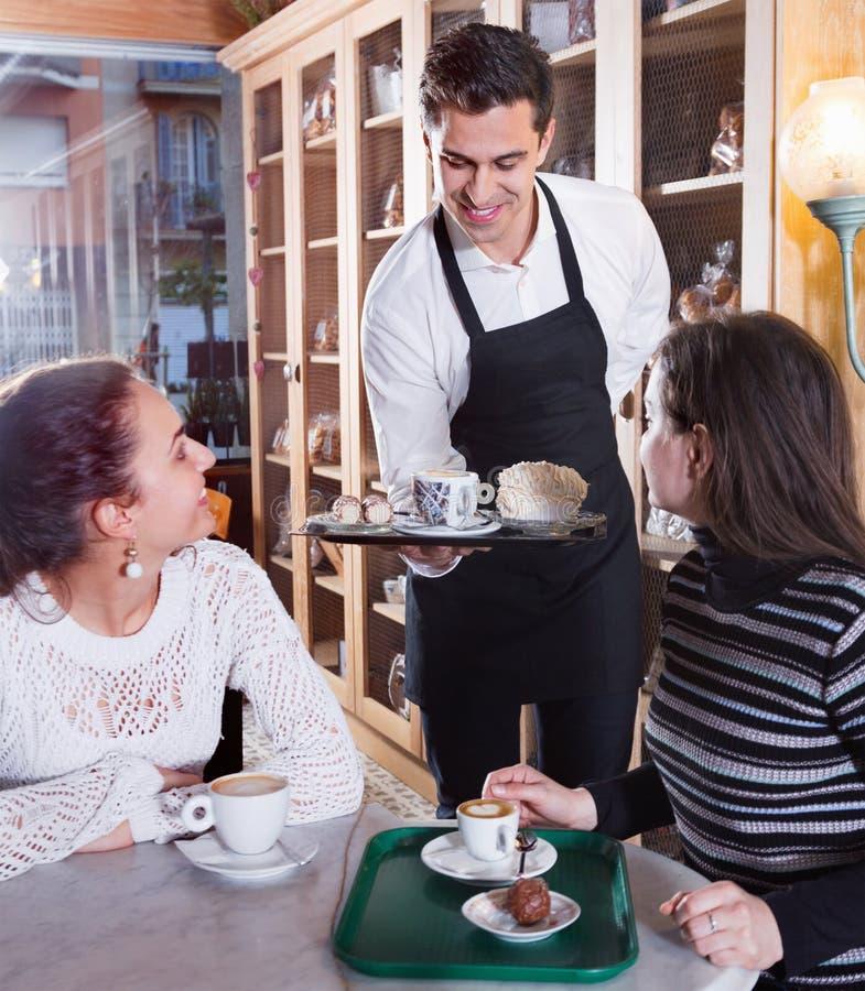 Положительная сервировка официантки испечет и печенье для девушек стоковое изображение rf