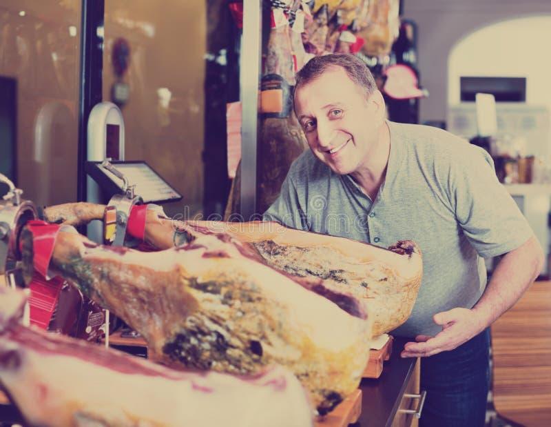 Положительная середина постарела мужской клиент покупая вкусное jamon стоковое фото