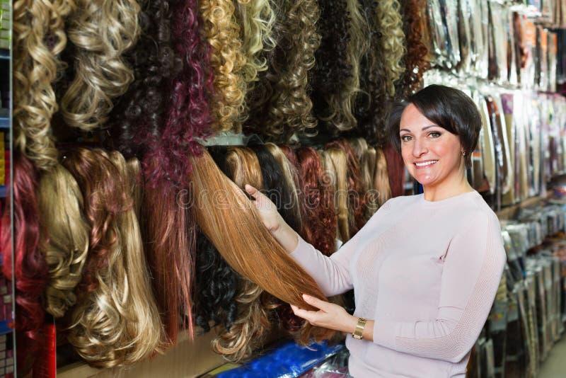 Положительной женщина постаретая серединой покупая расширение волос стоковые изображения
