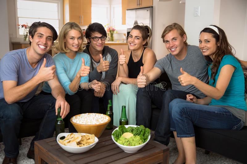 Положительные большие пальцы руки вверх по группе в составе друзья собрали дома сидеть в живущей комнате на праздник торжества па стоковое изображение