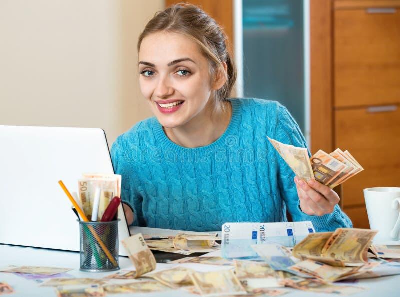 Положительные деньги заработка молодой женщины быть фрилансером стоковые фотографии rf
