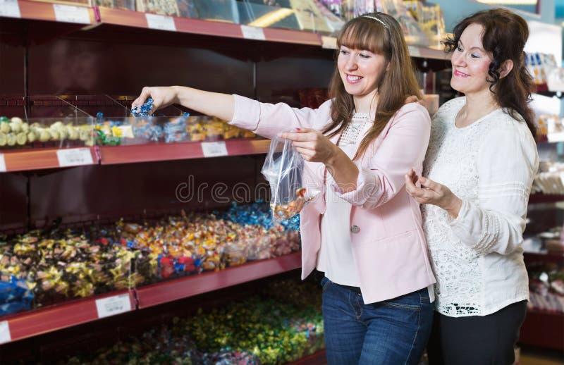 Положительные женские покупатели выбирая традиционные конфеты стоковое фото rf