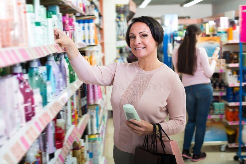 Положительные женщины выбирая сливк от полки стоковые фотографии rf