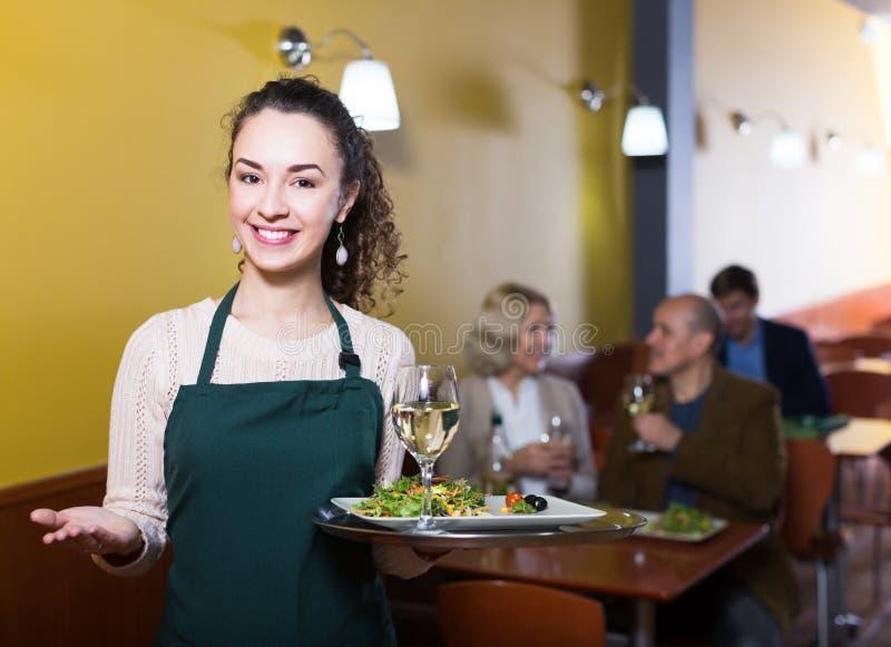 Положительные клиенты приветствию официантки стоковое изображение rf