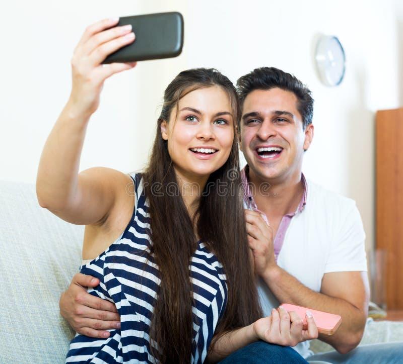 Положительные молодые супруги представляя и делая selfie стоковая фотография