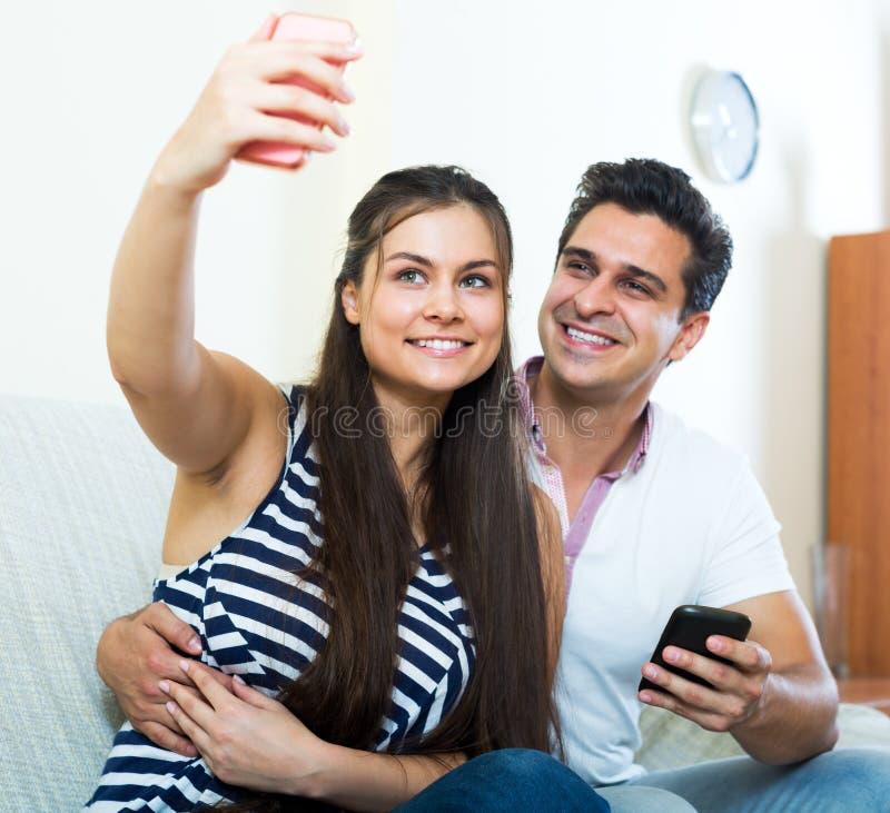 Положительные молодые супруги представляя и делая selfie стоковая фотография rf