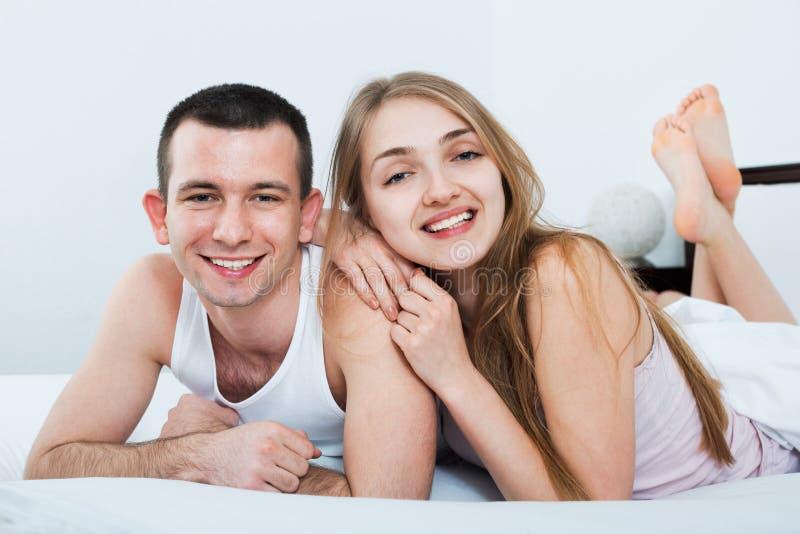 Положительные молодые счастливые взрослые лежа в семье кладут в постель стоковые изображения
