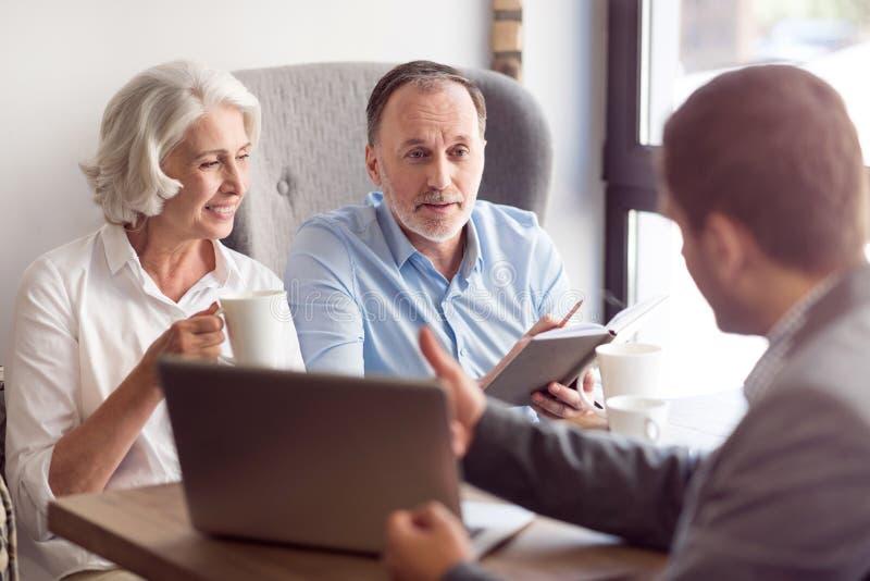 Положительные старшие пары разговаривая с администраторов по сбыту стоковое фото rf