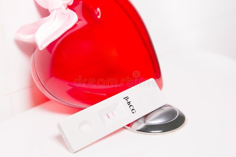 Положительные тест на беременность и сердце стоковое фото