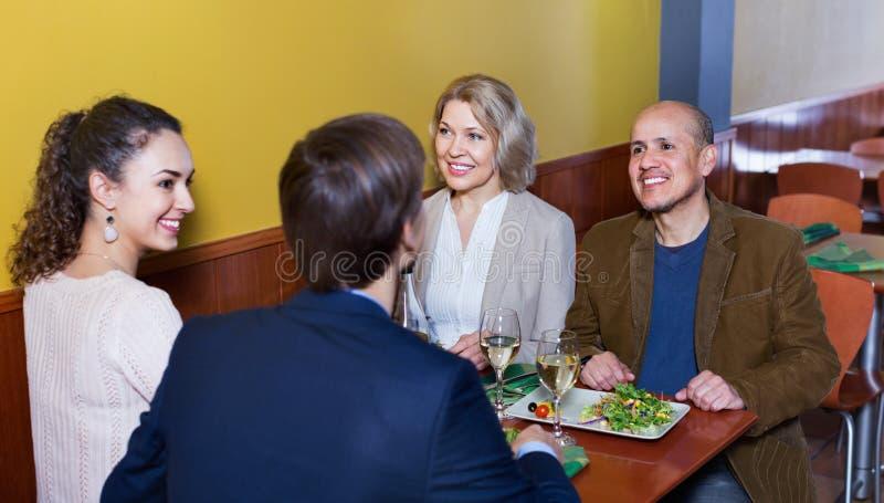 Положительные люди среднего класса наслаждаясь едой и вином стоковые изображения rf