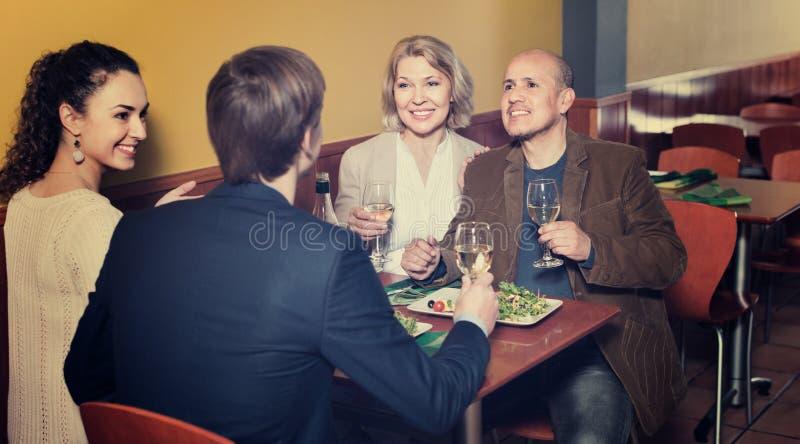 Положительные люди среднего класса наслаждаясь едой и вином стоковое изображение rf