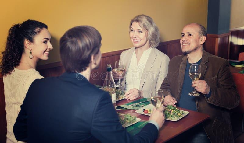 Положительные люди среднего класса наслаждаясь едой и вином стоковое изображение