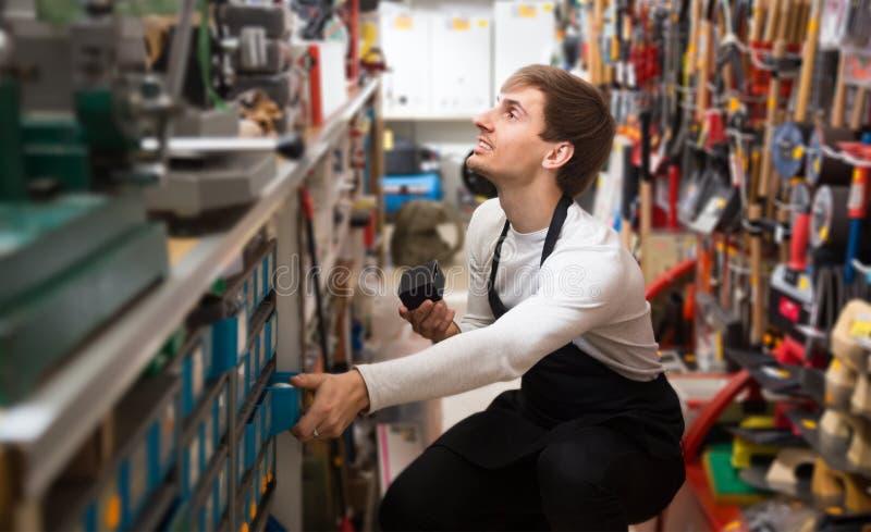 Положительный молодой мужской продавец в рисберме с инструментами стоковая фотография rf