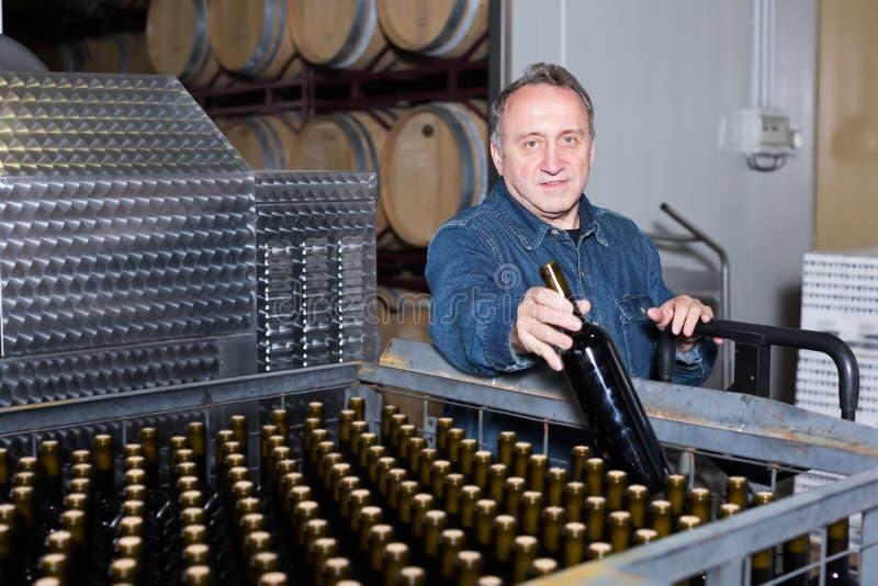 Положительный создатель вина проверяет контейнеры стоковое фото